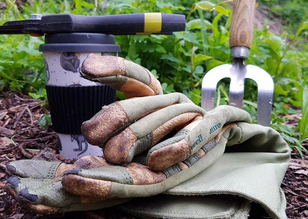Coffe cup with weeding tools and gloves